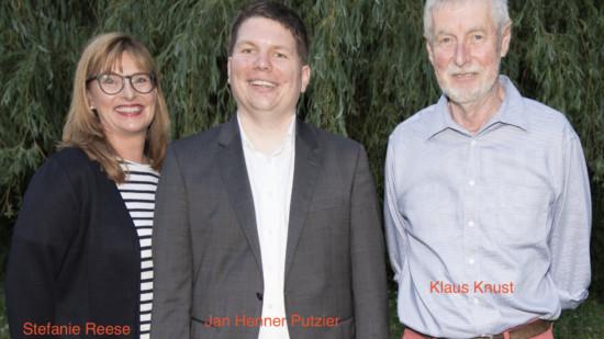 Drei Personen vor einer Weide.