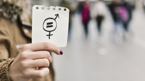 Auf dem Bild ist der Oberkörper einer Frau zu sehen, die einen Notizzettel in das Bild hält. Darauf zu sehen sind die verflochtenen Piktogramme für Männer und Frauen und darin ein =-Zeichen.
